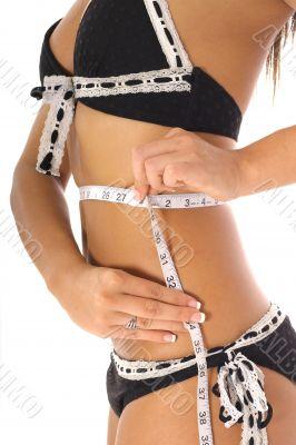 woman taking measurements in a bikini