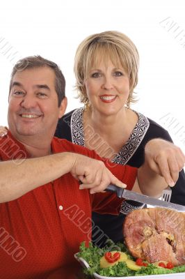 couple carving a ham