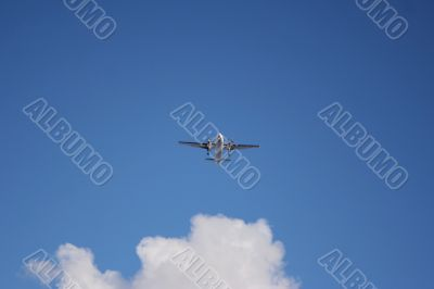 Plane on a blue and cloudy sky