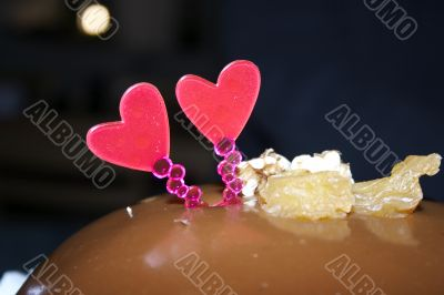 Glazed chocolate cake with two red lovely hearts