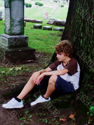boy feeling sad sitting under a tree