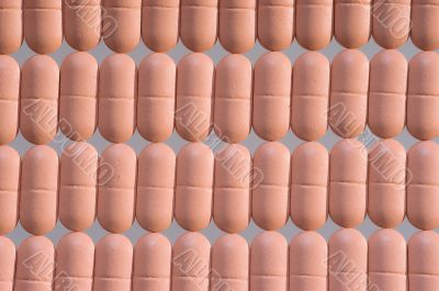 Rows of pink pills over grey