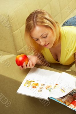 The girl lays on a sofa, reads the magazine