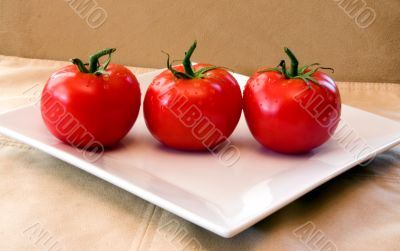 3 red vine ripened tomatoes on a white plate.