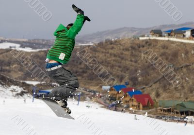 Snowboarder jumping at contest in mountains