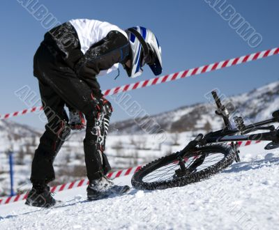Snow biker downhill in winter mountains