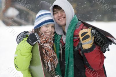 A lifestyle image of two teens snowboarders