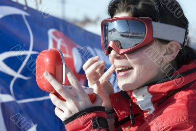 Attractive sport girl snowboarder applying face