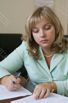 A serious business woman is studying documents