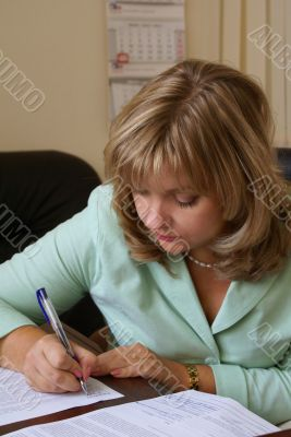 A serious business woman is signing contract