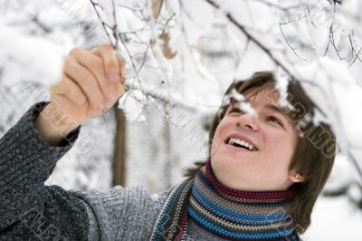 Teens boy with snown branch in winter