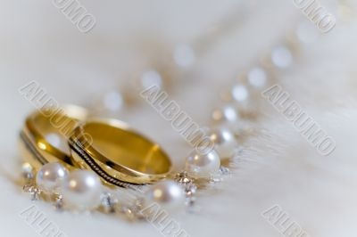 Two rings and pearl necklace lying on a white fur