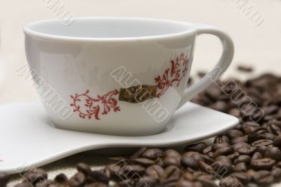 Cup of coffee and grains over sackcloth