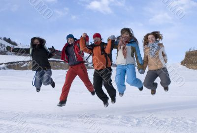 Group of sports teenagers jumping in mountains