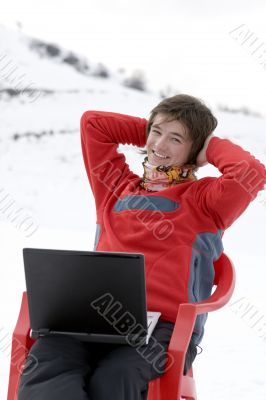 Happy teens with laptop in winter mountains