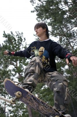 Teenager in Camouflage jumping by Skateboard