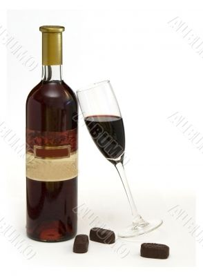 Bottle and wineglass with wine and chocolate candy
