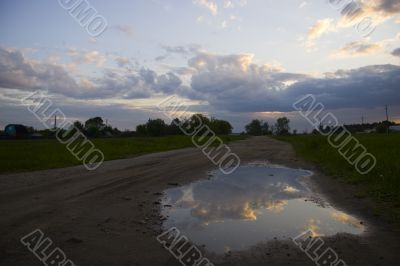 Clearing sky reflected in a puddle
