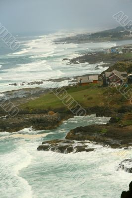 Surf with homes along rugged coastline