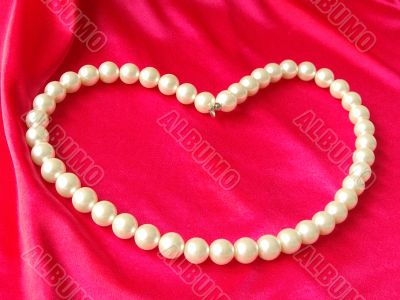 Heart from pearls on a red background