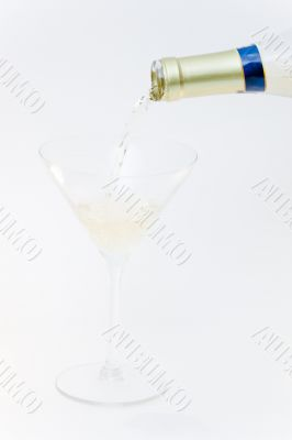 Filling one glass with wine by holding in hand bottle
