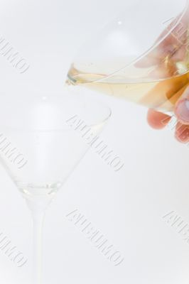 Filling one glass with wine by holding in hand another glass