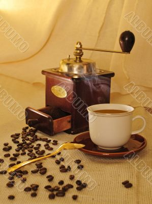 Cup of coffee with coffee mill and beans