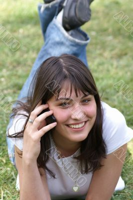 Smiling girl in a park with sell phone