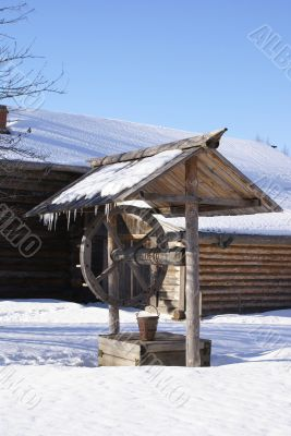 Old wooden house and draw-well