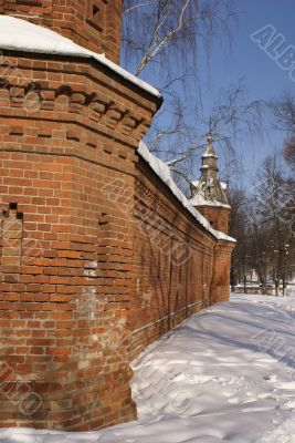Old tall red brick wall of with decorated towers