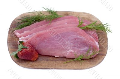Raw pork schnitzel with dill and a strawberry