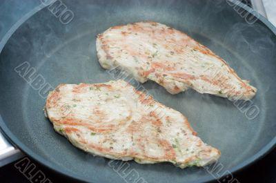 Fried schnitzel on a teflon frying pan