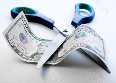 Scissors cutting through dollar note