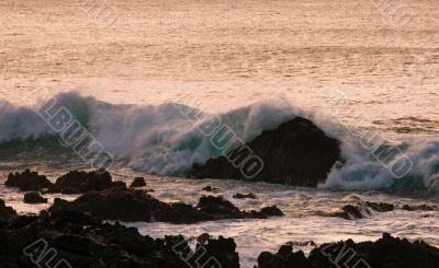 Crashing waves on rock in sunset