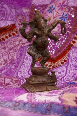 Bronze Ganesha dancing, on purple