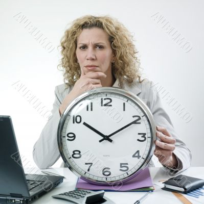 Woman pondering with clock