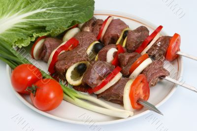 Appetizing shish kebab with vegetables and greens