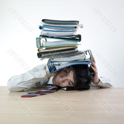 Businessman`s head crunched by folders