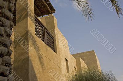 An arabic house balcony shaded by palm trees