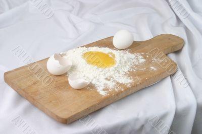 Eggs and a flour on a board