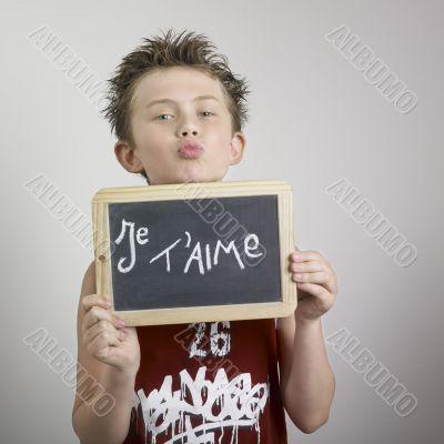 Boy and blackboard with je t`aime written on it