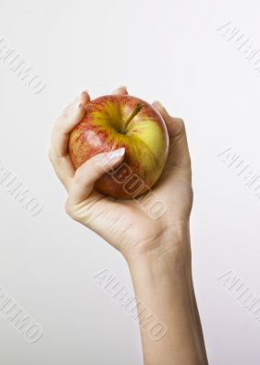 Hand gripping apple