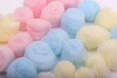 Yellow, blue and pink hygienic cotton balls in rows