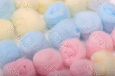 Blue, yellow and pink hygienic cotton balls in rows