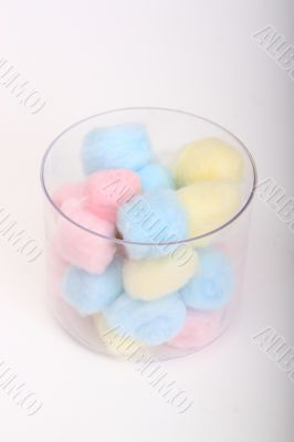 Blue and pink hygienic cotton balls in a glass canister