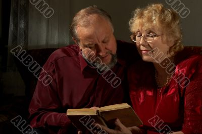 Happy elderly spouses behind reading
