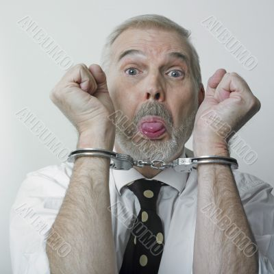 Man and handcuffs sticking out his tongue