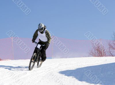 Professional winter biker in mountains at contest