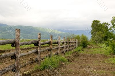Green pasture and wood fence at mountains