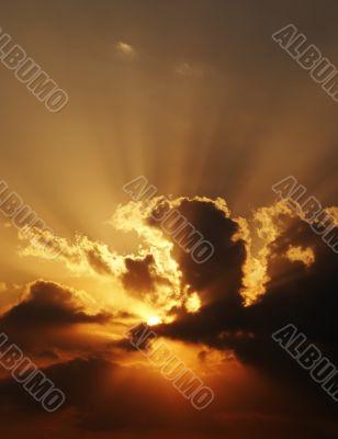dramatic sundown scene with dark clouds and rays